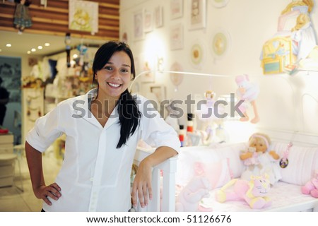 portait of small business owner: proud woman opening her baby shop - stock photo