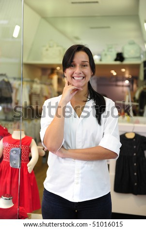 portait of small business owner: proud woman opening her children clothing shop - stock photo