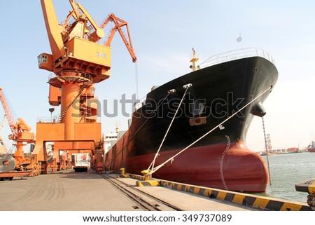 Portal crane and cargo ship, closeup of photo - stock photo