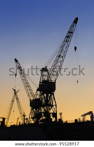portal cranes in Riga shipyard at the sunset - stock photo