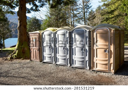 Portapotty, or portable enclosed plastic portable toilet with chemicals and deodorizers in a tank, in a park yard for public convenience - stock photo