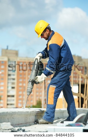 Portarait of positive Builder worker with pneumatic hammer drill equipment at construction site - stock photo