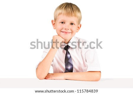 portarat of  elementary schoolboy sitting a table isolated over white - stock photo