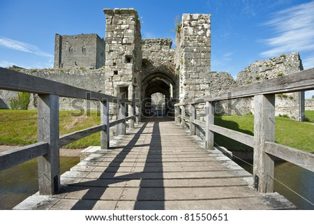 Portchester Castle in Hampshire viewed over a wooden bridge on a beautiful day - stock photo