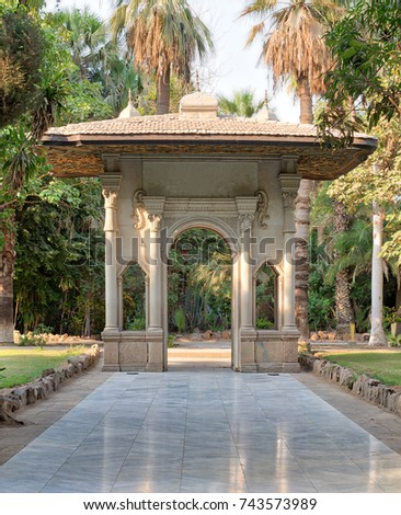 Porte-cochere (carriage porch, Gate) at a public park with marble tiled floor, trees and palms, Cairo, Egypt