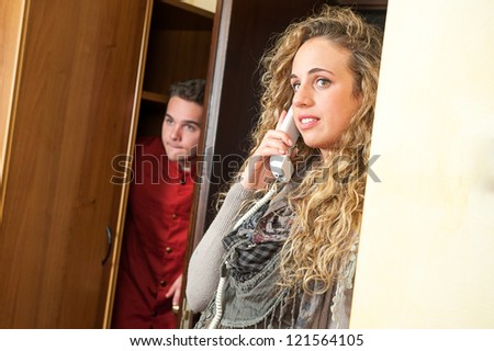Porter listen at the door a fascinating girl at the phone - stock photo