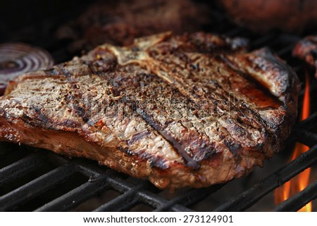 Porterhouse steak on a barbecue, shallow depth of field.
