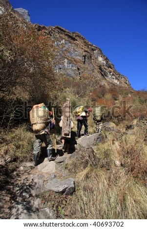 Porters carry load in the Annapurnas Nepal. - stock photo