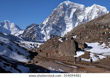 Porters, hikers from Lobuche to Everest Base Camp, with crystal clear view of Mt Tobuche, Upper Khumbu, Nepal. At 5000 m above sea level, the snow does not melt during daytime. - stock photo