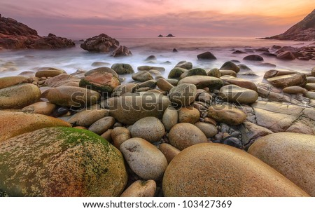 Porth Nanven cove in West Cornwall is a fine example of a glacial valley, the rock formations are smooth and rounded, the valley is near St Just has the Brison rocks not far offshore. - stock photo