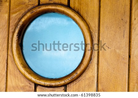 Porthole in old wooden ship's door with great blue sky visible through the glass - stock photo