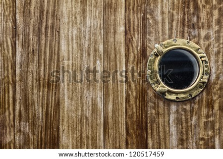 porthole with window on wooden planks of an old ship - stock photo