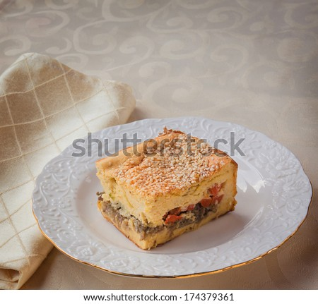 Portion cheese souffle stuffed with carrots, meat and cabbage on a white plate - stock photo