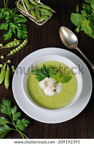 Portion cream soup with green peas with mint cream  - stock photo