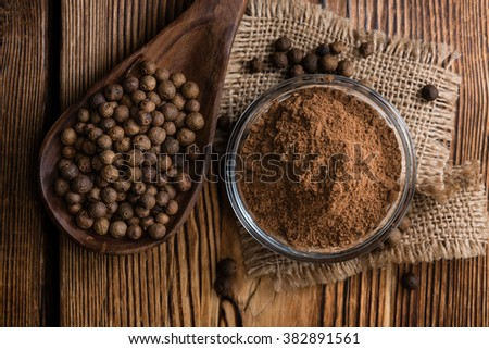 Portion of Allspice powder (detailed close-up shot) on wooden background - stock photo