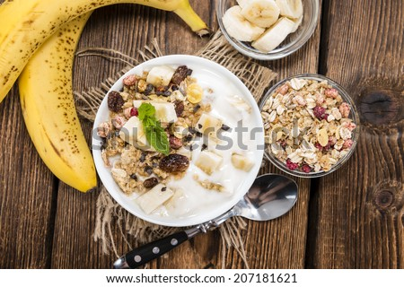 Portion of Banana Yogurt in a bowl with honey and muesli - stock photo