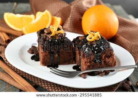 Portion of Cake with Chocolate Glaze and orange on plate, on wooden background - stock photo