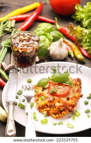 Portion of casserole with tomato and mushrooms on a plate - stock photo
