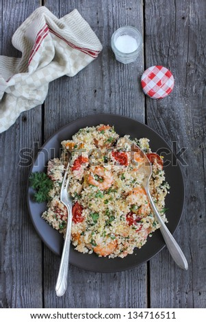 Portion of cauliflower couscous with roasted garlic shrimps, cherry tomatoes, lemon juice and zest and chopped fresh parsley in a plate ready to eat - stock photo