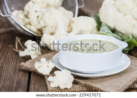 Portion of Cauliflower Soup (on rustic wooden background) - stock photo