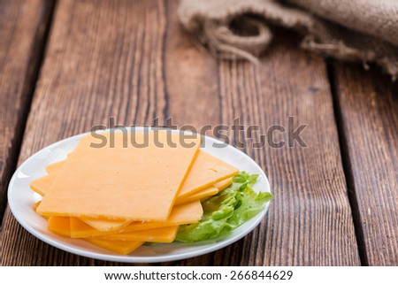 Portion of Cheddar Slices on wooden background (close-up shot) - stock photo