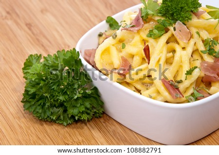Portion of Cheese Spaetzle decorated with Parsley on wooden background (macro view) - stock photo