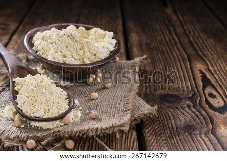 Portion of Chick Pea flour on vintage wooden background - stock photo
