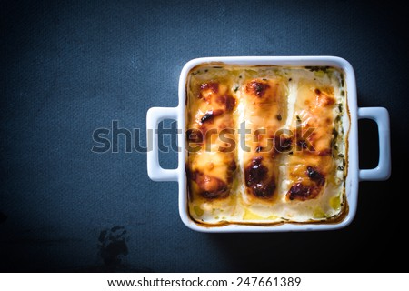 POrtion of chicken meat stuffed with ham and cheese with blank space on the left side  - stock photo