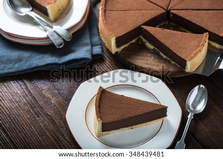 Portion of chocolate tort or cake on plate on wooden table