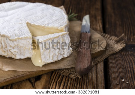 Portion of creamy Camembert (detailed close-up shot) on rustic wooden background