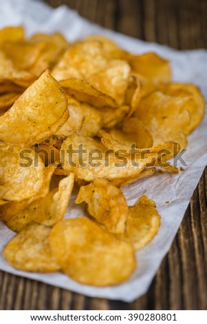 Portion of crispy Potato Chips (selective focus) on wooden background - stock photo