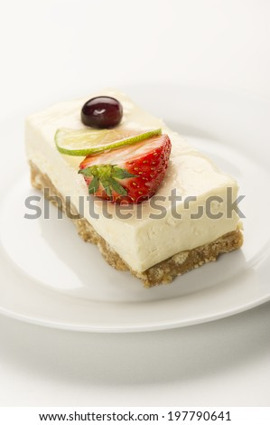 Portion of delicious creamy lemon or lime cheesecake on a pastry base topped with a slice if lime and strawberry , high angle close up view in vertical format with copyspace - stock photo