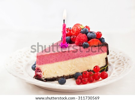 Portion of delicious raspberry cheesecake decorated with fresh berries, chocolate and candle - stock photo