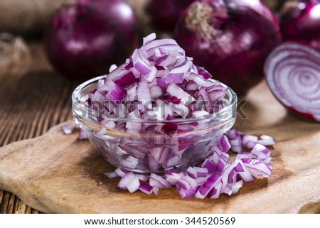 Portion of diced Red Onions (close-up shot) on an old rustic wooden table - stock photo