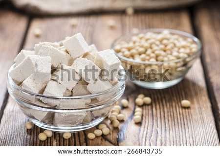 Portion of diced Tofu (detailed close-up shot) on wooden background - stock photo