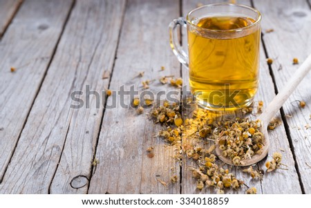 Portion of dried Camomile (close-up shot) on an old wooden table - stock photo