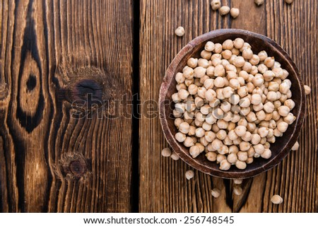 Portion of dried Chick Peas on an old wooden table - stock photo