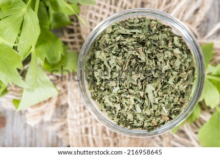 Portion of dried Lovage (detailed close-up shot) with fresh leaves on wood - stock photo