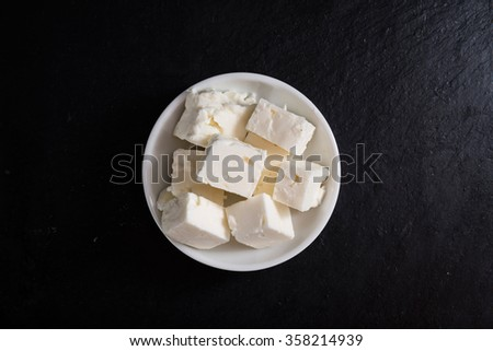 Portion of Feta Cheese on slate (selective focus, close-up shot)