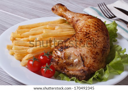 Portion of French fries with chicken leg and cherry tomatoes on a white plate. close-up - stock photo