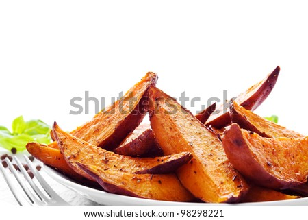 Portion of fresh baked sweet potato wedges - stock photo