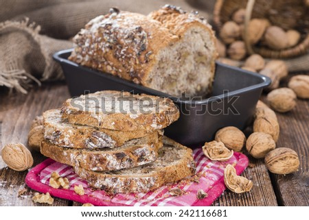 Portion of fresh baked Walnut Bread on dark wooden background - stock photo
