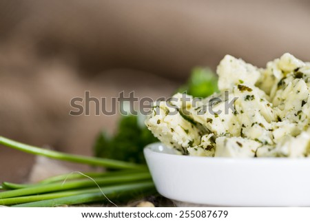 Portion of fresh made herb butter on rustic wooden background - stock photo