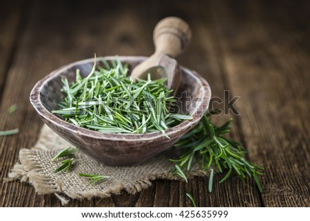 Portion of fresh Rosemary as a detailes close-up shot (selective focus) on wooden background