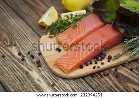 Portion of fresh salmon fillet with aromatic spices and herbs on a wooden background - stock photo