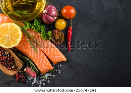 Portion of fresh salmon with spices,herbs and vegetables on black slate background - stock photo