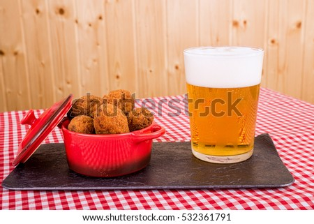 Portion of freshly fried cod fish croquettes served with beer, a Spanish tapa