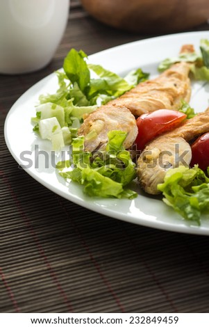 Portion of fried fish served with fresh salad - stock photo