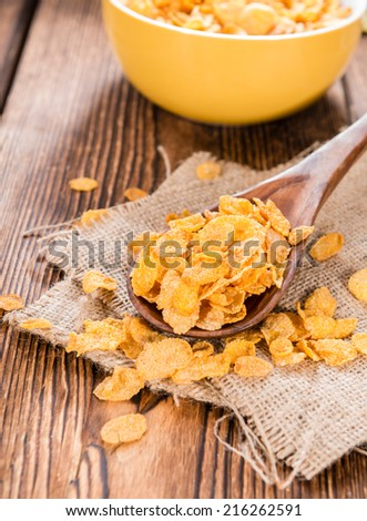 Portion of golden Cornflakes on wooden background (close-up shot) - stock photo