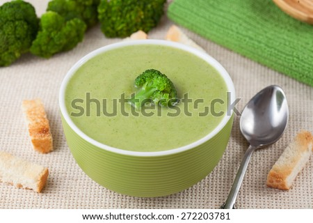Portion of green broccoli cream soup restaraunt recipe with croutons on textile background - stock photo